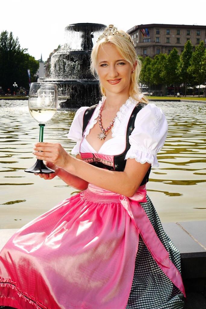 Die Wiesbadener Weinkönigin Stephanie Kopietz begleitet den Weinwoche-Motivwagen beim Festumzug. Foto: luxtempi