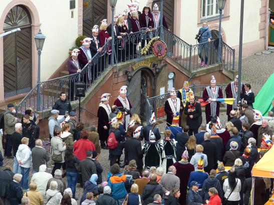 Die Dachorganisation Wiesbadener Karneval 1950 e.V. (DACHO) hat heute um 11.11 Uhr vor dem Rathaus feierlich die Fahne gehisst. Mit dabei: OB Sven Gerich (SPD, M. mit rotem Mikro), der DACHO-Vorstand, das Prinzenpaar Harald I. (mit langer Feder an der Narrenkappe) und Jasmine I. und viele Neugierige. Foto: Sabine Voß/Stadt Wiesbaden